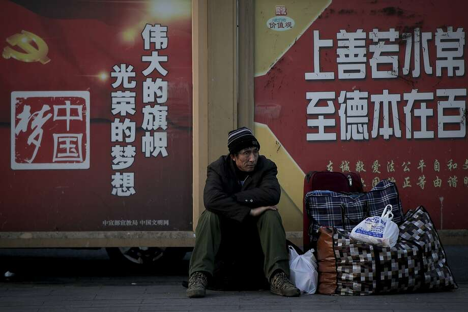A migrant worker sits next to his belongings against a wall displaying a Chinese government propaganda message at the Beijing railway station. Photo: Andy Wong / Associated Press