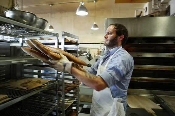 Chad Robertson of Tartine Bakery and Cafe removes bread from an oven on Friday, Sept. 14, 2014 in San Francisco, Calif.