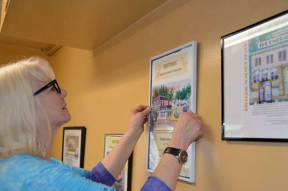 Elizabeth Wright hangs framed posters of old Walnut Beach/Myrtle Beach scenes at Alfas Pizza on Naugatuck Avenue. The art, including the one at left, is based on old postcards and history of the beach area. Photo: Jill Dion / For Hearst Conn. Media