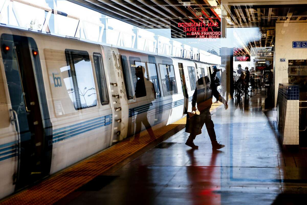 FILE -- Passengers are seen through a reflection at MacArthur BART Station on Friday, November 2, 2018 in Oakland, Calif. A person on the tracks is causing a 20-minute delay for riders Wednesday afternoon.