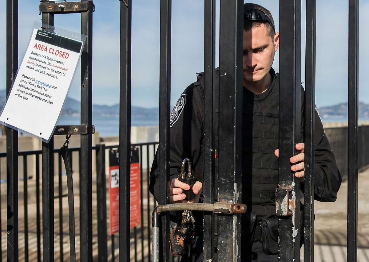 A federal parks police officer enters the shuttered Aquatic Park Pier to remove trespasses after the pier was closed as the result of a partial government shutdown at the San Francisco Maritime National Park in San Francisco, Calif. Saturday, Dec. 22, 2018.