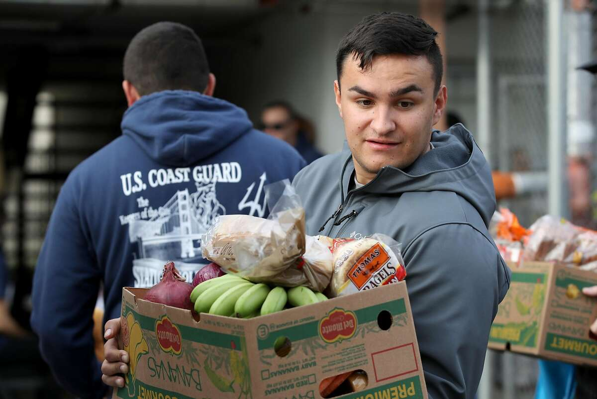 NOVATO, CALIFORNIA - JANUARY 19: A U.S. Coast Guard member carries a box of free groceries during a food giveaway on January 19, 2019 in Novato, California. As the partial government shutdown enters its fourth week, an estimated 150 U.S. Coast Guard families in the San Francisco Bay Area, who are currently not being paid, received free groceries during an event organized by the San Francisco-Marin Food Bank and the North Bay Coast Guard Spouses Club. (Photo by Justin Sullivan/Getty Images)