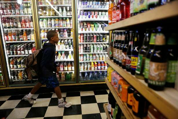 Zaire Lowrey, 12, walks past the sodas sitting in the fridges at Ashby Supermarket on Friday, April 14, 2017, in Berkeley, Calif.