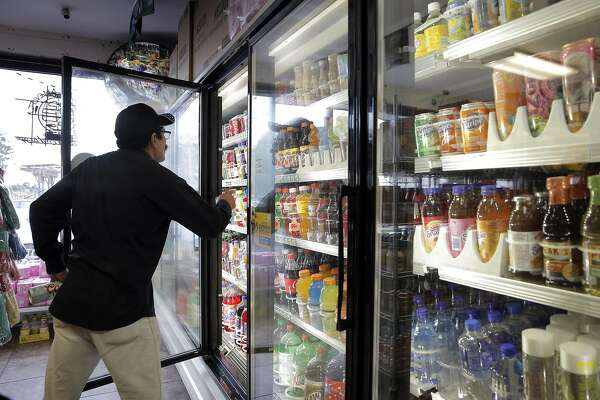 Francisco Serrano looks for a soda at US Liquor Beer & Wine store in Berkeley, Calif., on Monday, August 22, 2016. A new UC-Berkeley study shows that Berkeley's first-of-its-kind-in-the-nation tax on sodas and other sugary drinks has led to a drop in soda consumption in the city's most low-income neighborhoods.