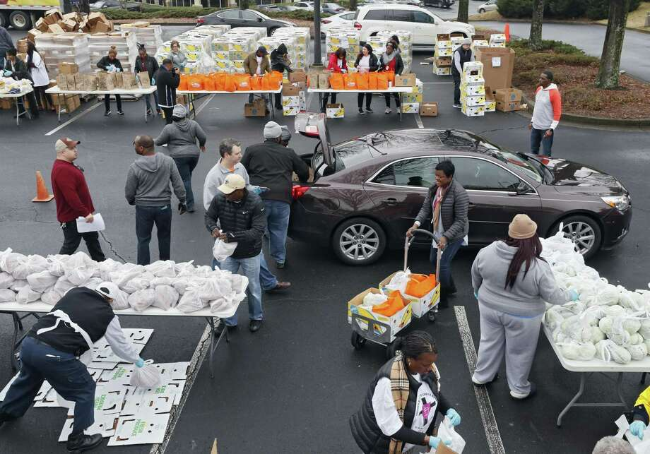 Employees from the Transportation Security Administration and Customs and Border Protection and their families wait in line for groceries from the Atlanta Community Food Bank and Antioch Baptist Church in Hapeville, Ga., last week. The shutdown is having a ripple effect. Photo: Bob Andres /Associated Press / 2018 Atlanta Journal Constitution