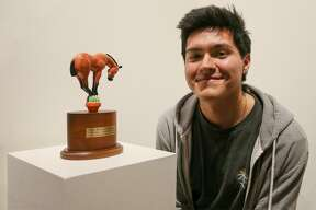 """Joseph Casas, 17, a senior at at Wagner High School, shows his sculpture titled """"Horse Balancing on Cactus,"""" which is on display in the Briscoe Western Art Museum. Casas was awarded an $8,000 scholarship for winning the sculpture category in the 23rd annual San Antonio Stock Show & Rodeo Student Western Art Contest."""