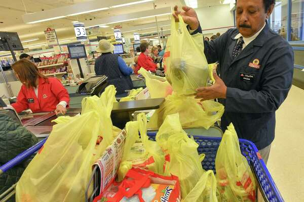 Mahabubur Kahn, a bagger at ShopRite, bags a customers order on April. 27, 2018. A plastic bag ban goes into effect in the city in May.