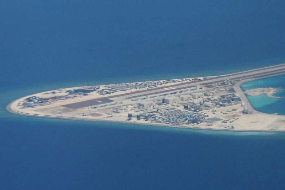 FILE - In this Friday, April 21, 2017, file photo, an airstrip, structures, and buildings on China's man-made Subi Reef in the Spratly chain of islands in the South China Sea are seen from a Philippine Air Force C-130 transport plane of the Philippine Air Force.  (AP Photo/Bullit Marquez, File) Photo: Bullit Marquez / Copyright 2017 The Associated Press. All rights reserved.