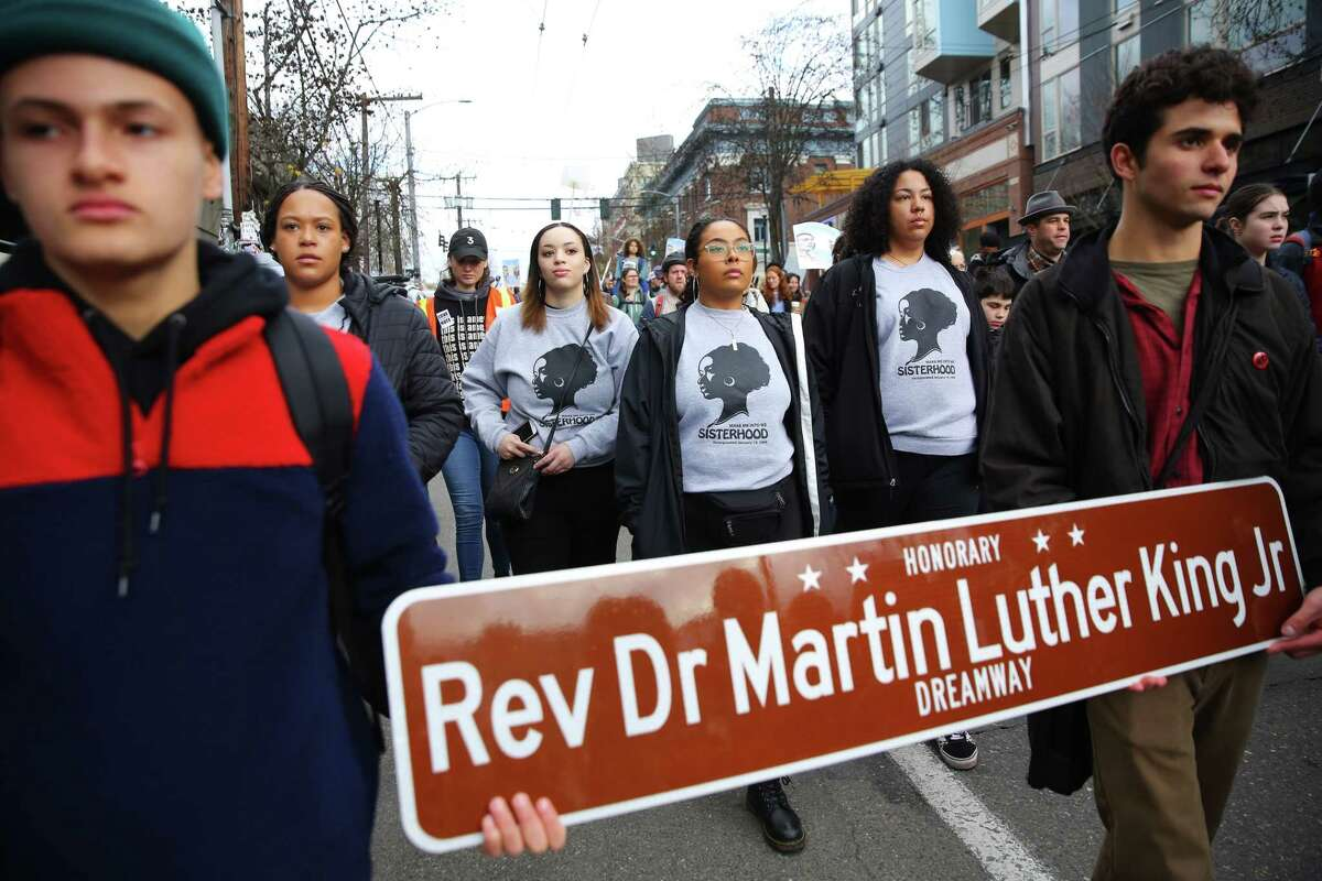 Bainbridge High School students Spencer Bispham, left, and Andres Rovalo carry a street sign with the name of Dr. Rev. Martin Luther King Jr. on it as thousands march from Garfield High School to Westlake Park as a part of Seattle's annual MLK Day celebration, Monday, Jan. 21, 2019. Other MLK Day events included rallies, an opportunity fair, workshops and youth activities.