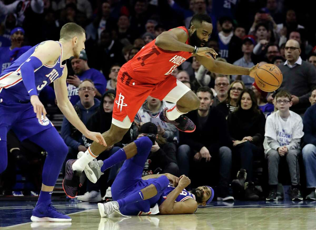 Houston Rockets' James Harden, top, leaps over Philadelphia 76ers' Corey Brewer as Mike Muscala looks on during the first half of an NBA basketball game, Monday, Jan. 21, 2019, in Philadelphia. (AP Photo/Matt Slocum)