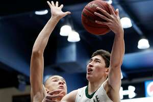 De La Salle's Tim Kostolansky scores against San Joaquin Memorial's Braxton Meah in 1st quarter during De La Salle's 53-47 win in MLK Classic at St. Mary's College in Moraga, Calif., on Monday, January 21, 2019.