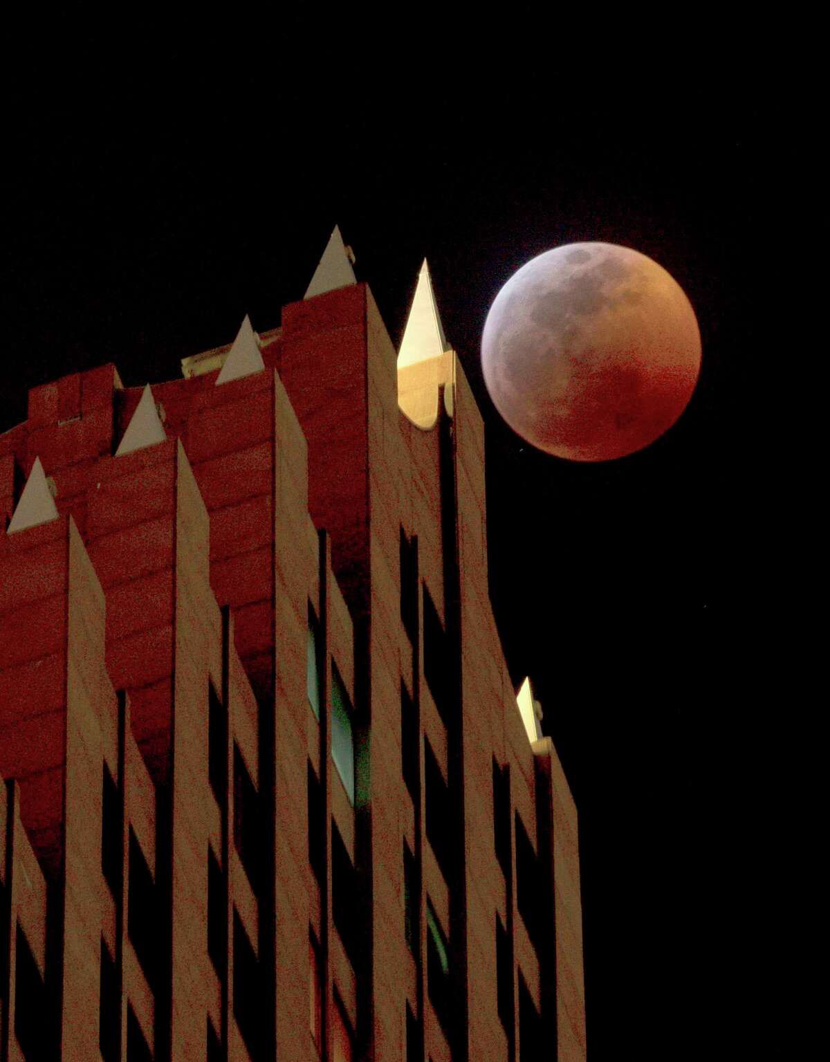 A super blood wolf moon eclipse occurs behind the Bank of America Center building in downtown Houston, Sunday, Jan. 20, 2019. The moon was fully covered by the Earth's shadow over Houston around 10:30 p.m. Sunday night.