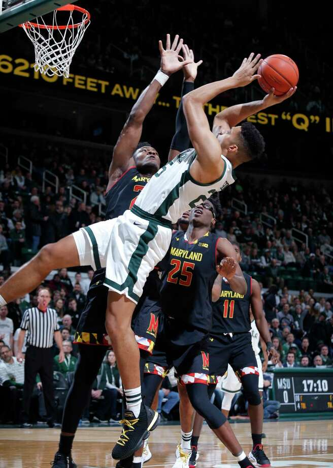 Michigan State's Kenny Goins shoots against Maryland's Bruno Fernando, left, and Jalen Smith (25) during the first half of an NCAA college basketball game, Monday, Jan. 21, 2019, in East Lansing, Mich. Michigan State won 69-55. (AP Photo/Al Goldis) Photo: Al Goldis / Copyright 2019 The Associated Press. All rights reserved