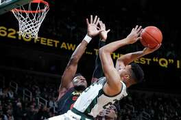 Michigan State's Kenny Goins shoots against Maryland's Bruno Fernando, left, and Jalen Smith (25) during the first half of an NCAA college basketball game, Monday, Jan. 21, 2019, in East Lansing, Mich. Michigan State won 69-55. (AP Photo/Al Goldis)