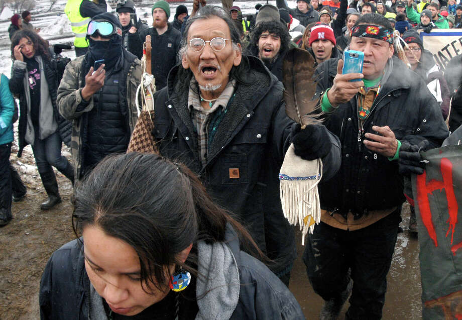 FILE - In this Feb. 22, 2017, file photo, a large crowd representing a majority of the remaining Dakota Access Pipeline protesters, including Nathan Phillips, center with glasses, march out of the Oceti Sakowin camp before the deadline set for evacuation of the camp near Cannon Ball, N.D. Phillips says he felt compelled to get between a group of black religious activists and largely white students with his ceremonial drum to defuse a potentially dangerous situation at a rally in Washington. (Mike McCleary/The Bismarck Tribune via AP, File) Photo: Mike McCleary / The Bismarck Tribune
