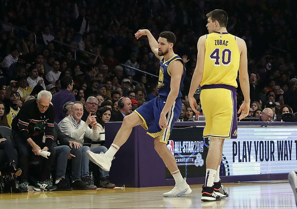 Golden State Warriors' Klay Thompson, center, celebrates after making a 3-point basket next to Los Angeles Lakers' Ivica Zubac (40) during the second half of an NBA basketball game, Monday, Jan. 21, 2019, in Los Angeles. (AP Photo/Marcio Jose Sanchez)
