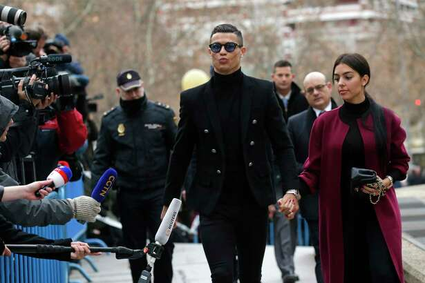 Cristiano Ronaldo arrives at the court in Madrid on Tuesday, Jan. 22, 2019. Cristiano Ronaldo is expected to plead guilty to tax fraud. The Juventus forward arrived in a black van, walked up some stairs leading to the court house and stopped to sign an autograph. The charges stem from his days at Real Madrid.