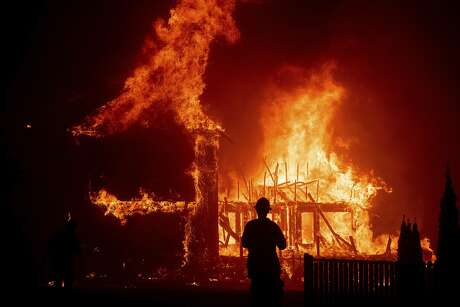 FILE - In this Nov. 8, 2018, file photo, a home burns as the Camp Fire rages through Paradise, Calif. Officials are looking for more stable housing for roughly 600 people still sleeping at a Northern California fairground following the deadly wildfire last year. (AP Photo/Noah Berger, File)
