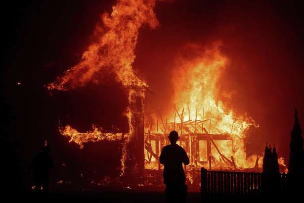 A home burns in November 2018 as the Camp Fire rages through Paradise, Calif. (AP Photo/Noah Berger, File)