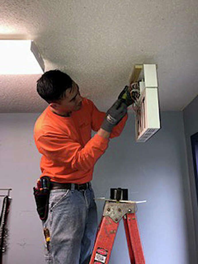 Dave Balai, a maintenance electrician for the Southern Illinois Univeristy at Edwardsville, works on installing a LED exit sign at the Metro East Humane Soceity as part of an Eagle Scout's project this past weekend. Photo: For The Intelligencer