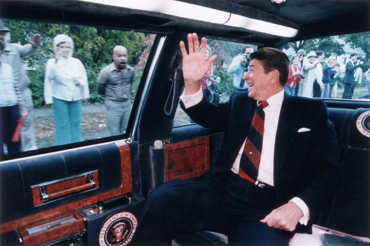 US President Ronald Reagan waves from the back of his limousine to a line of people on the street as he heads toward a campaign stop in Fairfield, Connecticut, 26th October 1984.