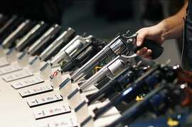 FILE - In this Jan. 19, 2016 file photo, handguns are displayed at the Smith & Wesson booth at the Shooting, Hunting and Outdoor Trade Show in Las Vegas. When gunmakers and dealers gather this week in Las Vegas for the industry's largest annual conference, they will be grappling with slumping sales and a shift in politics that many didn't envision two years ago when gun-friendly Donald Trump and a GOP-controlled Congress took office. (AP Photo/John Locher, File)