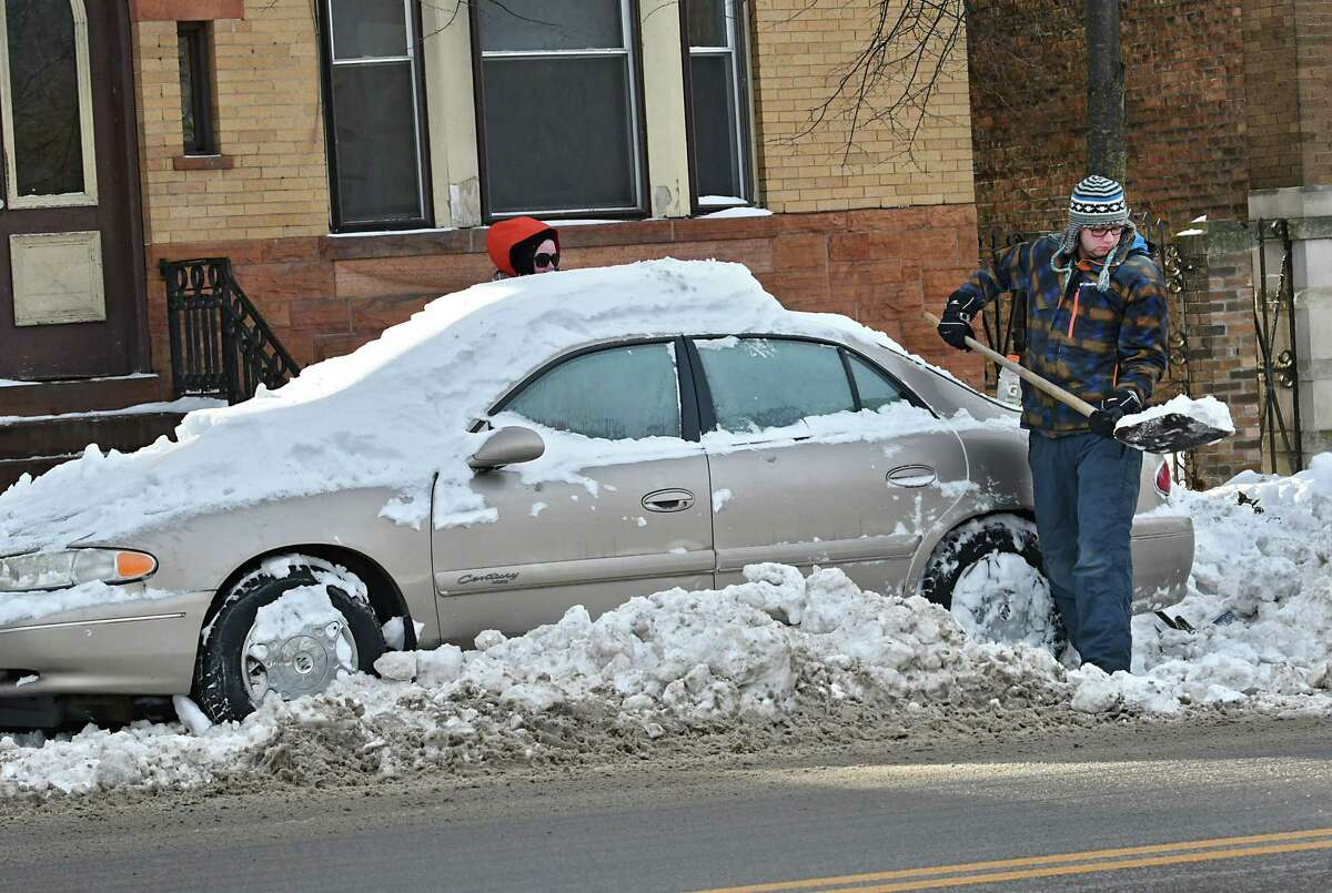 Will Behan of Albany, right, and his girlfriend Shea Stoughton dig out of a parking spot on Madison Ave. on Tuesday, Jan. 22, 2019 in Albany, N.Y. The couple wanted to move their car for the snow emergency after a major snowstorm on Sunday. (Lori Van Buren/Times Union)