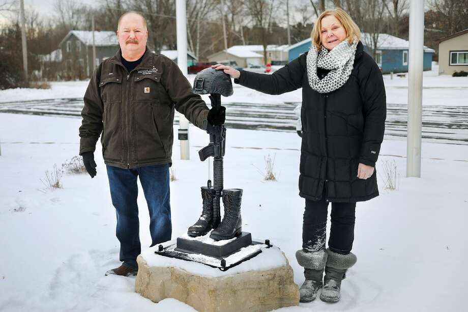 Jon and Kim Burgess pose for a portrait on Tuesday, Jan. 22, 2019 with a bronze battlefield cross, the newest addition to the Sanford Flag Memorial. The Burgesses lost their son, Lance Cpl. Ryan Burgess, on Dec. 21, 2006, in Iraq and formed the Ryan Burgess Memorial Foundation, which spearheaded the creation of the memorial at the Sanford Trailhead on the Pere Marquette Rail-Trail. (Katy Kildee/kkildee@mdn.net) Photo: (Katy Kildee/kkildee@mdn.net)