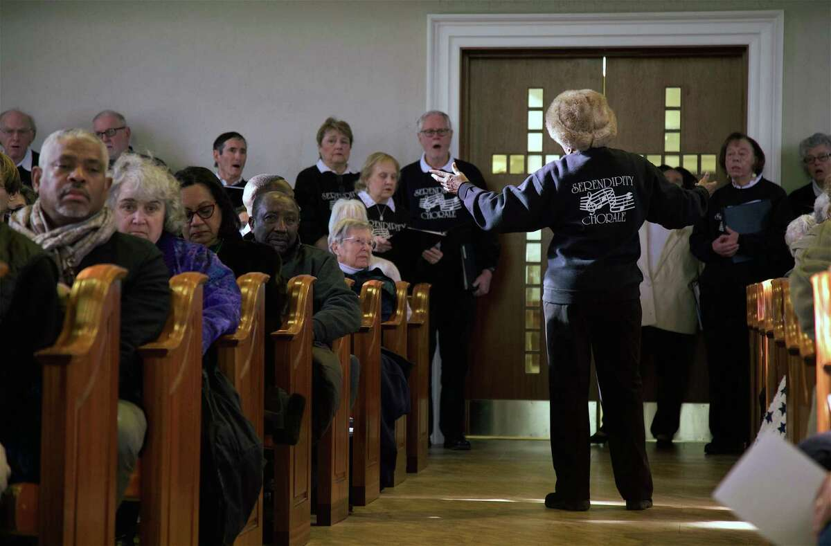 Gigi Van Dyke conducts the Serendipity Chorale at the back of the sanctuary at the 17th annual Interfaith Service for Martin Luther King, Jr., at United Methodist Church, Monday, Jan. 21, 2019, in New Canaan, Conn.