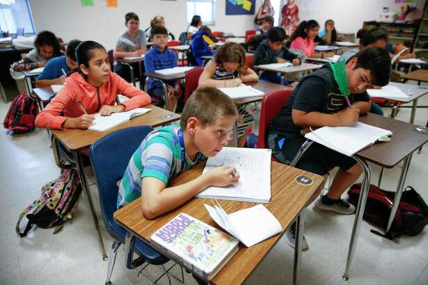 Cleveland Middle School sixth grader James Castro, 11, looks at the board as he writes in his notebook during reading class in one of the school's portables Monday Sept. 17, 2018 in Cleveland. Enrollment at Cleveland ISD has nearly doubled since 2014 from 3,800 to 6,500 students, straining the district and schools.