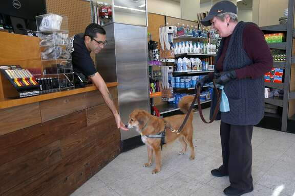 Karl Aguilar offers a doggie treat to Scout, while Chris Roebuck shops at the Papenhausen Hardware temporary store on West Portal Avenue in San Francisco, Calif. on Tuesday, Jan. 22, 2019. The pop-up store is open just a few doors down from its original location, which is being rebuilt after a fire gutted the store one year ago and will reopen in a few months.