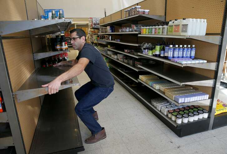 Karl Aguilar removes a shelf from a display case at the temporary Papenhausen Hardware store on West Portal Avenue in San Francisco, Calif. on Tuesday, Jan. 22, 2019. The pop-up store is open just a few doors down from its original location, which is being rebuilt after a fire gutted the store one year ago and will reopen in a few months.