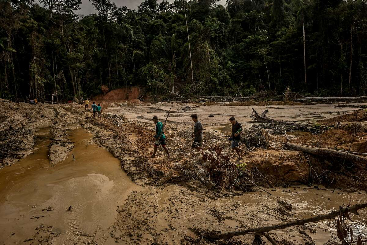FILE - Natives trek through lands destroyed by illegal gold prospecting in Brazil's Mundurucu Indigenous Territory, in the Amazon, March 31, 2018. As the far-right leader Jair Bolsonaro ascends to the presidency, Brazil has already begun backtracking from its role as a global exemplar of environmentally sustainable development. (Meridith Kohut/The New York Times)