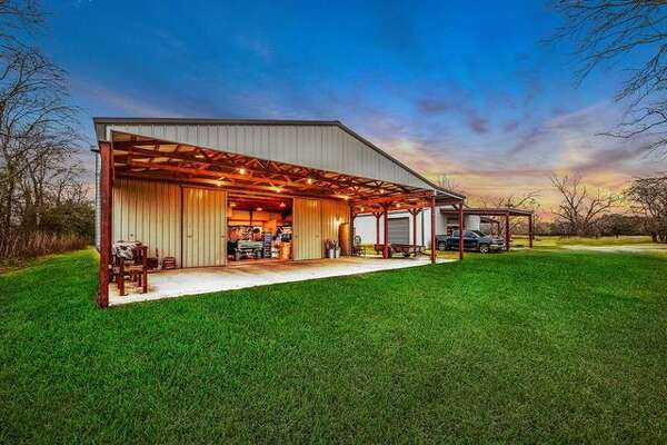 """2923 Krenek Road, Crosby, TX Price: $375,000 Off the beaten path barndominium: Situated on more than 6 lush acres with its own 320-feet-deep well, the building houses a one-bedroom residence with custom cabinetry, stained concrete floors, and a large upstairs storage space. The adjoining metal workshop also has its own bathroom. The listing adds that the property, which is described as being """"off the beaten path,"""" could be expanded by purchasing the adjoining 3 acres."""