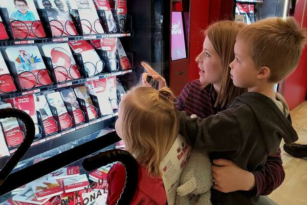 """Kaylene Stevens brought her two young children to make a donation using the """"Giving Machines"""" and teaches them about giving and helping others."""