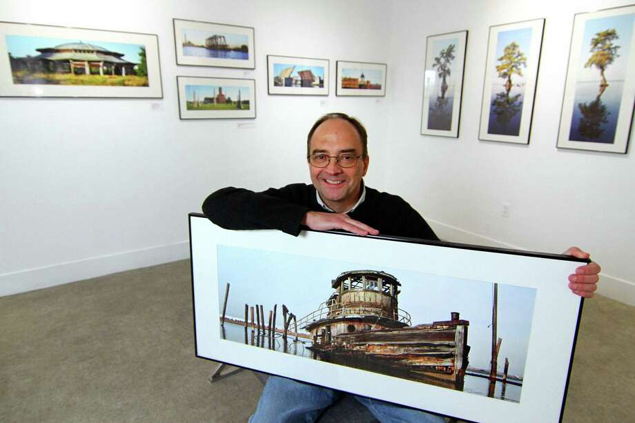 "Photographer Ned Gerard poses with one of his photographs at City Lights Gallery, in Bridgeport, Conn. Dec. 19, 2019. ""Forgotten Panoramas"", an exhibit of Gerard's photographs, is currently on display at the gallery. An opening reception will be held Thursday Jan. 24th from 5:30 p.m. to 8:30 p.m. Photo: Christian Abraham / Hearst Connecticut Media / Connecticut Post"