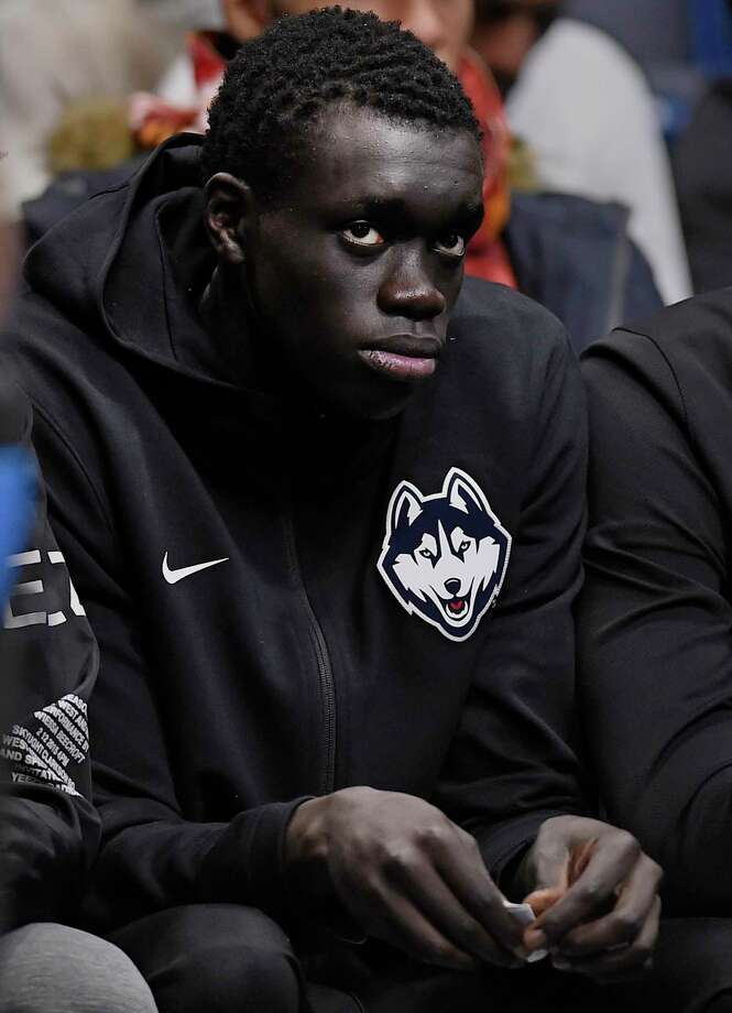 Basketball player Akok Akok watches an NCAA college basketball game between Connecticut and Arizona, Sunday, Dec. 2, 2018, in Hartford, Conn. Akok announced on Twitter that he has committed to Connecticut, but told reporters during the game that there is still a chance he could declare for the NBA draft. The 6-foot-9 forward plans to enroll for the spring semester and join the basketball team as a walk-on. (AP Photo/Jessica Hill) Photo: Jessica Hill / Associated Press / Copyright 2018 The Associated Press. All rights reserved