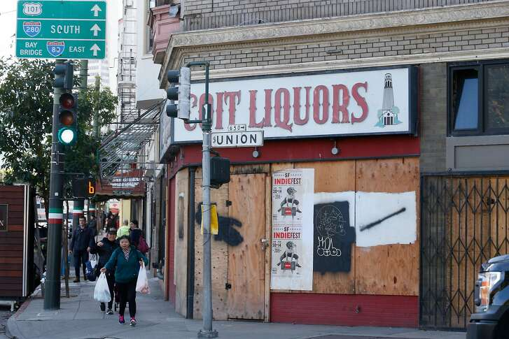 Pedestrians walk along Columbus Avenue past a boarded up storefront with Coit Liquors signage above it on Tuesday, January 22, 2019 in San Francisco, Calif.