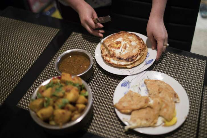 Rachana Shakya, 30, serves Baara and spiced potatoes, both Newari dishes at her home in Houston on Tuesday, Jan. 15, 2019.