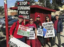"""Marianne O'Brien, second from right, and her fellow teachers pose in downtown Los Angeles after rallying at City Hall, Tuesday, Jan. 22, 2019. A tentative deal between Los Angeles school officials and the teachers union will allow educators to return to classrooms after a six-day strike in the nation's second-largest district. O'Brien said she was ready to support the contract but would consider voting """"No"""" if schools don't get additional support staff like nurses and counselors. (AP Photo/Christopher Weber)"""