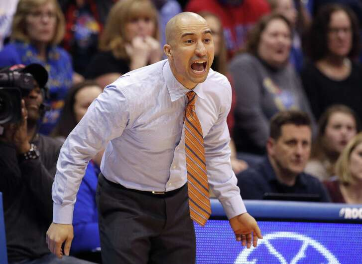 Texas head coach Shaka Smart talks to his players during the second half of an NCAA college basketball game against Kansas Monday, Jan. 14, 2019, in Lawrence, Kan. Kansas won 80-78. (AP Photo/Charlie Riedel)