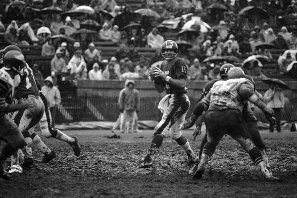 New York Giants quarterback Craig Morton looks downfield for a receiver late in the Giants Philadelphia Eagles game at Yale Bowl in New Haven, Connecticut, on Sunday, Dec. 8, 1974. Face to-face in front of Morton are Eagles Jerry Patton (77 in light jersey) and Giants Tom Mullen. Due to heavy rains, the field was a sea of mud. (AP Photo)