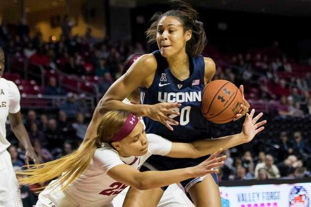 UConn's Olivia Nelson-Ododa, right, keeps the ball away from Temple's Mia Davis, left, on Saturday in Philadelphia.