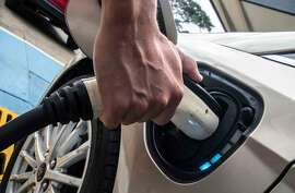 Costa Rican Roberto Quiros, owner of two electric cars, charges one of them at a Costa Rican Institute of Electricity (ICE) charging station in San Jose on December 4, 2018. - Electric vehicles slowly gain space in Costa Rica's congested streets, a country that prides itself on being an ecological paradise and works on an agenda to decarbonize its economy. Despite the 600 electric cars in private hands seem like a drop of water in a vehicle fleet of around 1.4 million, experts foresee an exponential growth. (Photo by Ezequiel BECERRA / AFP)EZEQUIEL BECERRA/AFP/Getty Images