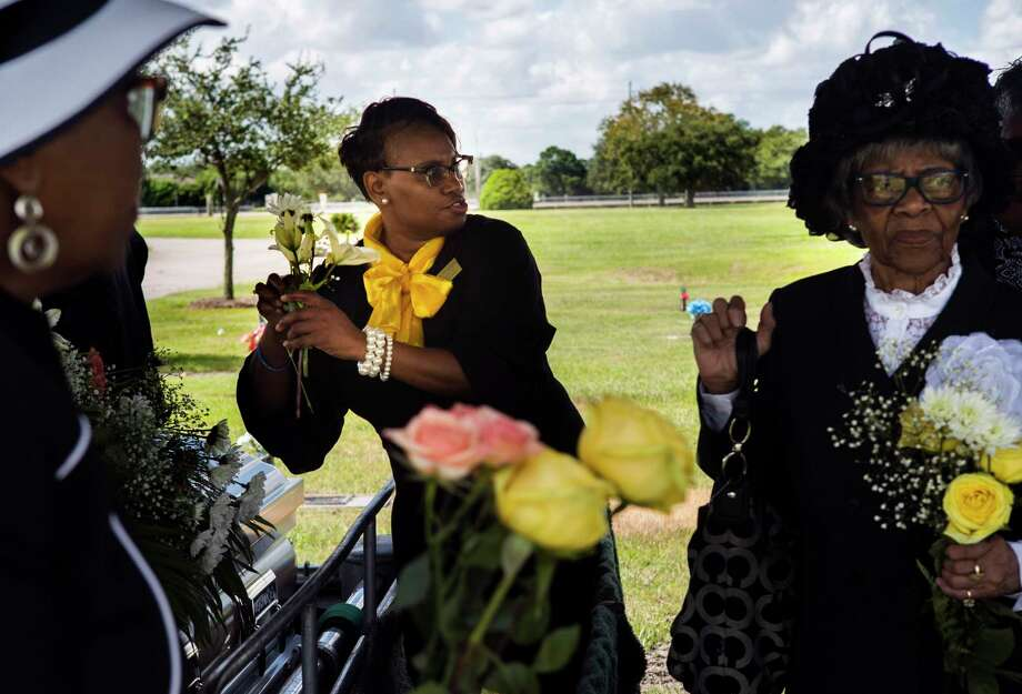 Ross Mortuary funeral attendant Yolanda Douglas, center, takes flowers from the casket to give them to the family of Ether Mae Fentis for keepsakes at the cemetery. Photo: Marie D. De Jesús, Staff Photographer / © 2018 Houston Chronicle