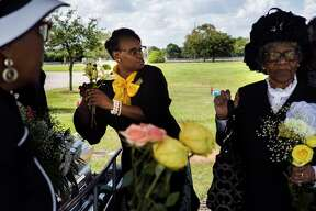 Ross Mortuary funeral attendant Yolanda Douglas, center, takes flowers from the casket to give them to the family of Ether Mae Fentis for keepsakes at the cemetery.