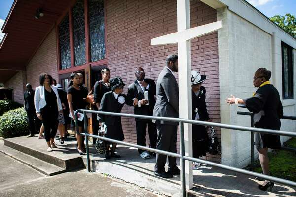 Ross Mortuary funeral attendant Yolanda Douglas, right, leads a mourning family to the limousines after the funeral of Ether Mae Fentis at Mt. Horem Baptist Church.
