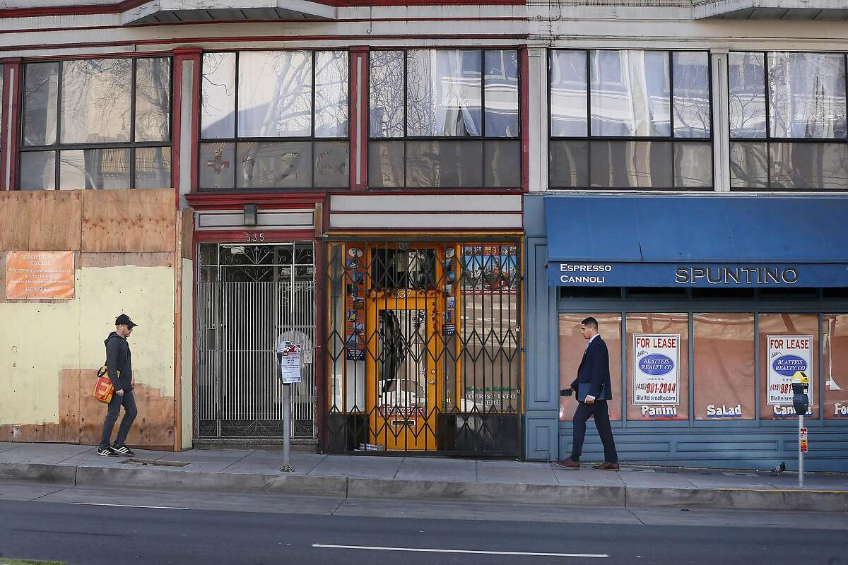Pedestrians walk past a vacant storefronts on Columbus Avenue on Tuesday, January 22, 2019 in San Francisco, Calif.