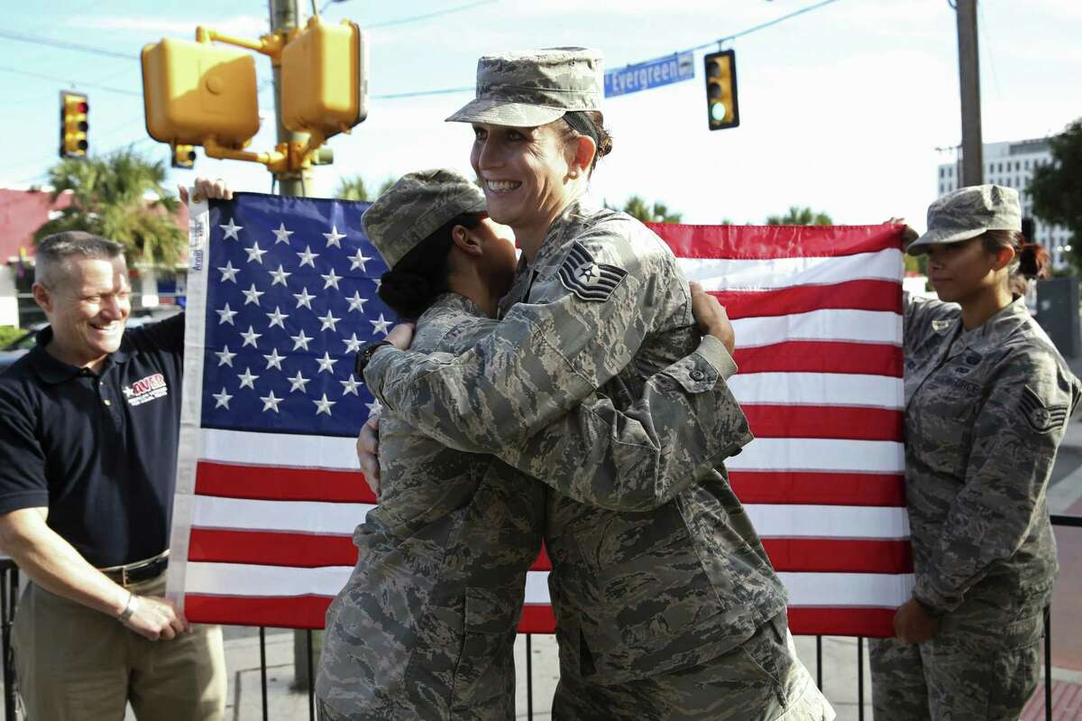 After swearing her reenlistment oath, Tech Sgt. Jamie Hash, right, hugs Staff Sgt. Dawnisha Peagler, during a swearing in ceremony at Luther's Cafe, Thursday, November 15, 2018. Hash, and other transgender individuals who are actively serving in the military will continue can do so under the Supreme Court's decision. Those who are not yet serving may be affected.