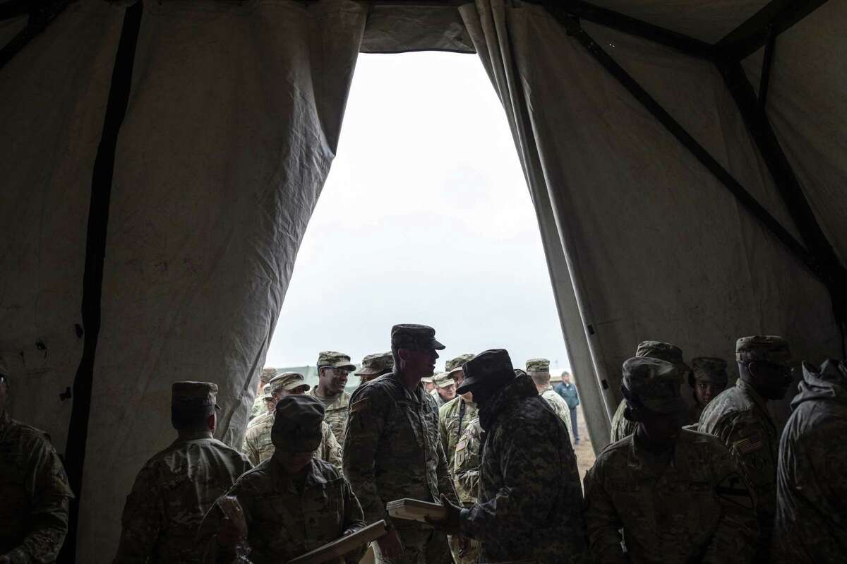 FILE-- U.S. Army soldiers line up to receive a Thanksgiving meal at Base Camp Donna, one of multiple military bases being set up along the U.S.-Mexico border, in Donna, Texas, Nov. 22, 2018. The Supreme Court on Jan. 22, 2019, allowed the Trump administration to proceed with its more restrictive policy against transgender recruits. In a brief, unsigned order, the justices temporarily stayed lower court decisions blocking the policy while lawsuits are pending. (Tamir Kalifa/The New York Times)